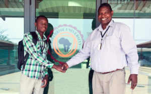 Brian Musentekwa shakes hands with Dr. Moffat Zimba